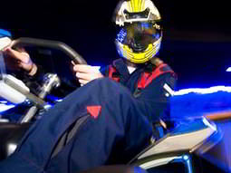 A close up of a man in a blue bodysuit, sat in a go kart