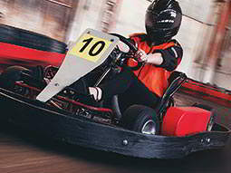 A man in a go kart on an indoor track