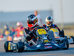 Two people racing on an outdoor karting track