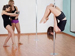 Image of two girls standing taking a photograph of a girl holding herself upside down on a pole