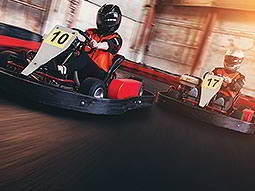 Two people racing go karts in helmets and overalls, on an indoor track