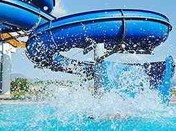 A blue slide going into a pool
