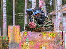A man in camouflage gear and a mask, stood behind a fence and aiming a paintball gun over the top