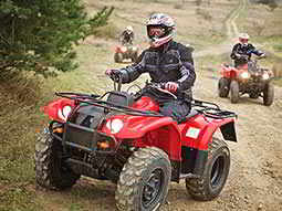 A man driving a red quad bike outside, with two others on quad bikes in the background