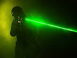 A man aiming a green laser from a laser gun to a smoky backdrop