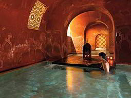 A woman in an indoor pool in an Arabian Baths