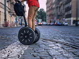 A mans legs driving a segway on a street