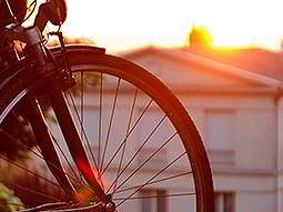 A bike wheel with a building in the background, at sunset