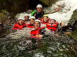 A group of people in helmets and life jackets, posing for a picture in water
