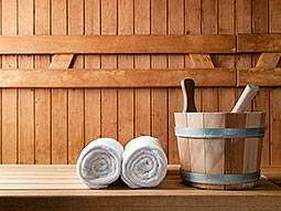 Two rolled up white towels next to a wooden bucket with paddles in, in a wooden sauna