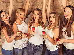 Five women in white vests, holding pink champagne glasses in front of them
