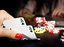 A womans hand lifting up two cards with poker chips in the background