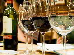 Close up of two glasses of red and white wine in a line, with a bottle in the background