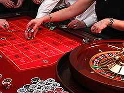 A woman's hands placing poker chips onto a table, with others around her