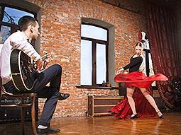 A man playing a guitar whilst a woman flamenco dances