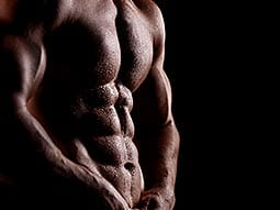 A man flexing his toned abdominal muscles against a black background
