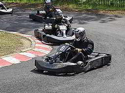 People racing on an outdoor go karting track