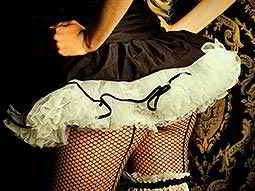 The back of a woman in fishnets and a black tutu dress