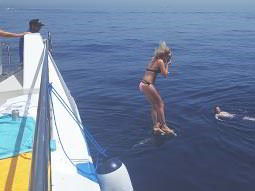A woman wearing a bikini jumps from the side of a white boat into the ocean
