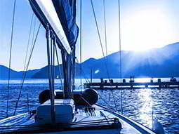 A white sailing boat with blue sea, mountains and bright sunlight in the background