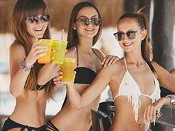 Three women in bikinis and sunglasses clinking yellow cups together in the air