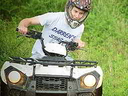 A man in a white stag shirt, driving a quad bike
