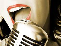 The bottom half of a womans face as she sings into a microphone