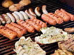 Close up of sausages, burgers, steak and chicken cooking on a barbecue