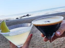 Close up of two people toasting with two cocktails