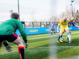 The back of a man in a green kit in goal, and two men in the background playing football