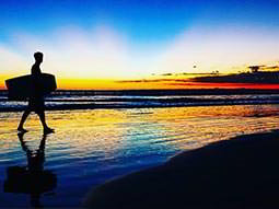 Silhouette of a man waking along the beach at sunset, and carrying a body board
