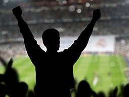 Silhouette of a man with his hands in the air, in the stands of a football ground