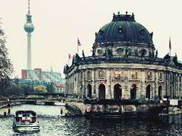 A grand old building in Berlin, with a boat sailing past on the river