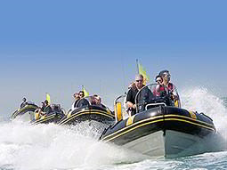 A line of four speedboats with people in them