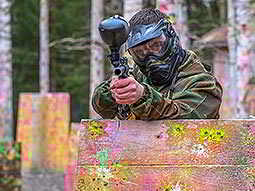 A man behind a barrier firing a paintball gun towards the camera