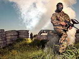 A man with a paintball gun sitting on a burnt out car, with piles of tyres in the background