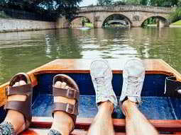 A womans feet and a mans feet on a boat, with the river and a bridge in the background