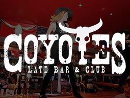 A woman in a black vest, jeans and cowboy hat dancing on top of a bar