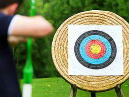 A man aiming at an archery target