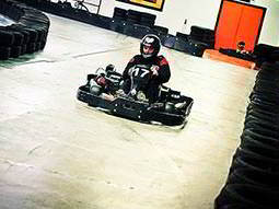 A person driving a go kart on a track, lined with tyres