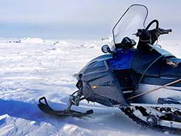 A snowmobile pictured on a large expanse of snow