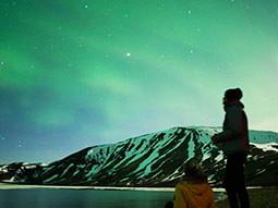 Two people silhouetted against some water, a mountain and a nighttime sky coloured green by the Northern Lights