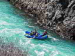 A blue raft being paddled down a bright blue river