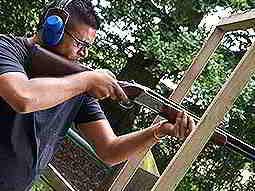 A man aiming with a shotgun through a wooden frame