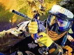 A man shooting paintball gun in camouflage gear and a mask