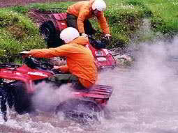 People driving quad bikes in water with steam coming off