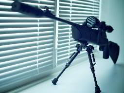 A close up of an air rifle on a stand in front of a window with the blinds shut