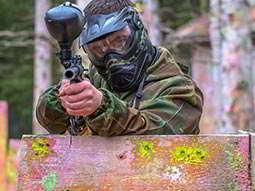 A person holding a gun whilst hiding behind a wooden obstacle