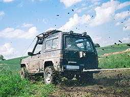 A large 4x4 driving through a muddy field