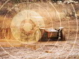 A faded image of a sniper target, over a faded image of a rage buggy driving through the mud